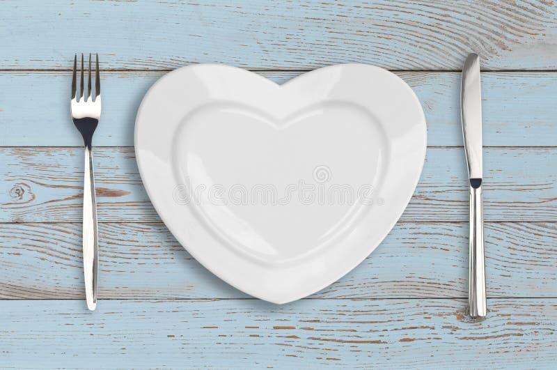 Vue supérieure de plat vide de coeur sur la table en bois bleue images libres de droits