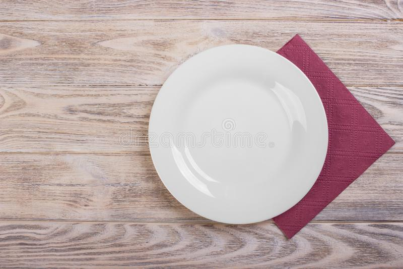 Vue supérieure de plat vide propre sur le dessus de table en bois avec la serviette photos stock