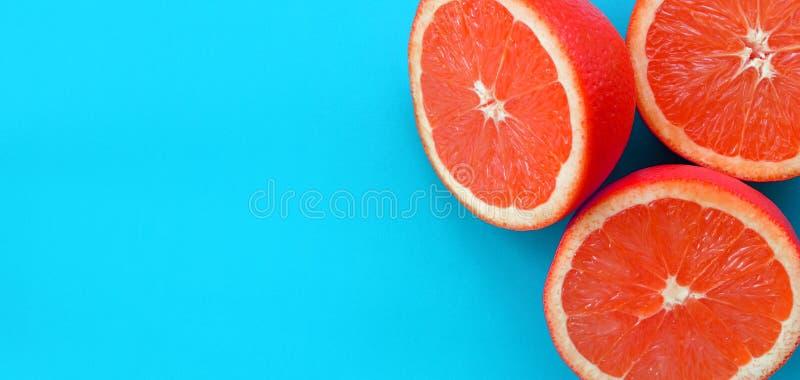Vue supérieure de plusieurs tranches d'un pamplemousse sur le fond lumineux dans la couleur bleue Une image saturée de texture d' images stock