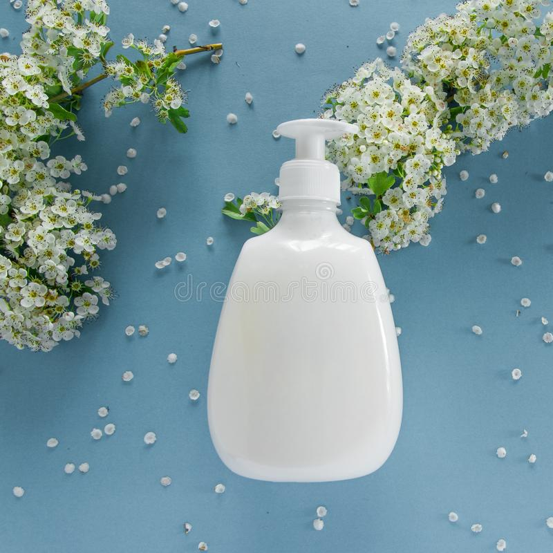 Vue supérieure de produit et de fleurs hygiéniques/cosmétiques sur le fond bleu mou Traitement de beauté de bien-être images libres de droits