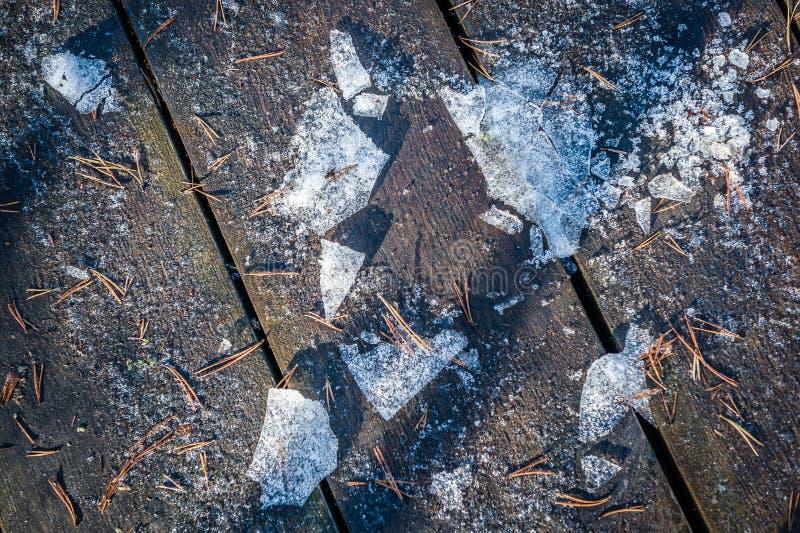 Vue supérieure de promenade en bois avec les premières aiguilles de neige, de glace et de pin Fond de texture Fin vers le haut Jo photo libre de droits