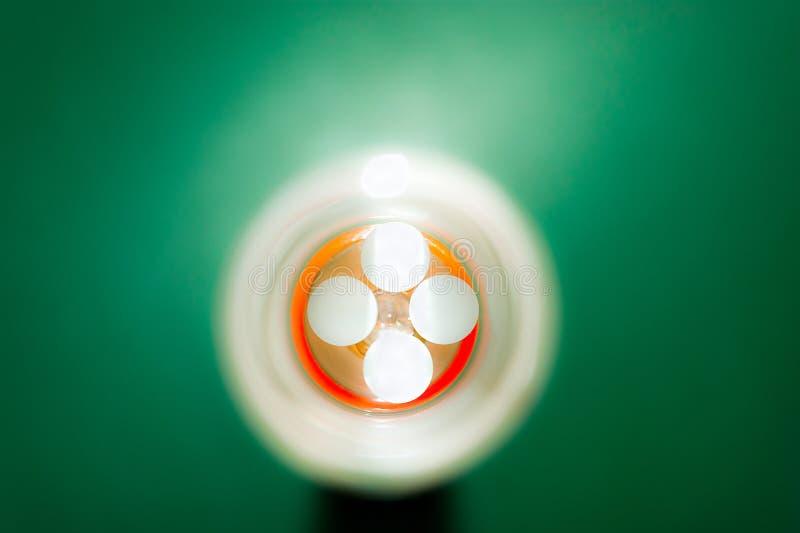 Vue supérieure de quatre pilules blanches de prescription au fond orange de la fiole sur le fond vert images libres de droits
