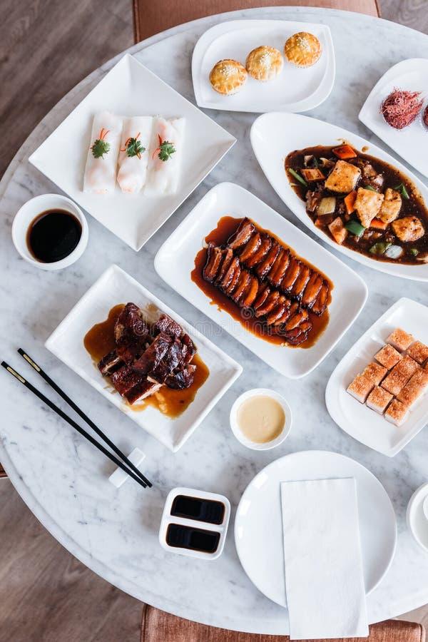 Vue supérieure de repas de Cantonese comprenant le porc de BBQ, canard rôti, ressort frais Rolls, filets cuits à la friteuse de c images stock