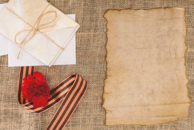vue supérieure de ruban de St George, oeillet, vieux papier vide, pile photographie stock