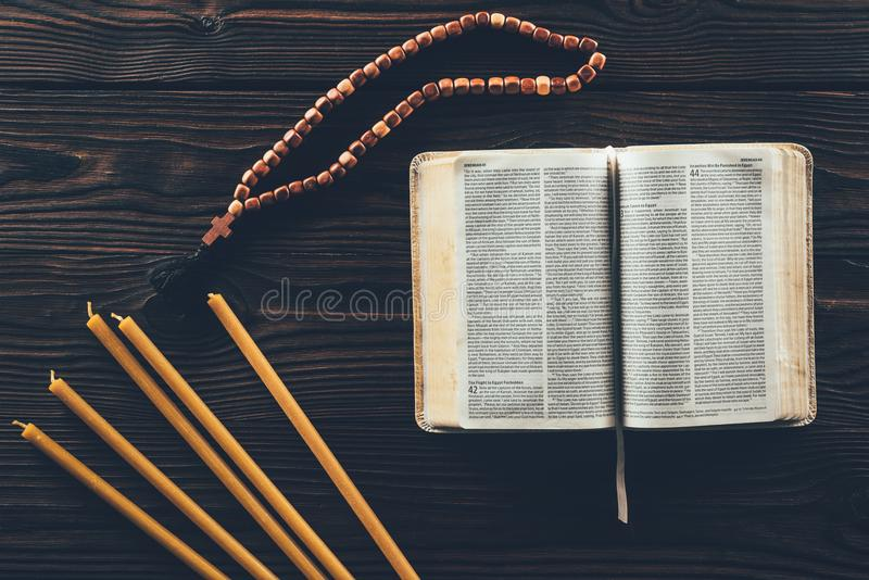 vue supérieure de Sainte Bible ouverte avec le chapelet et les bougies photo stock