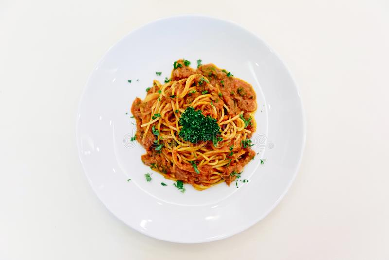 Vue supérieure de sauce à spaghetti avec le boeuf haché dans la cuvette blanche sur la nappe blanche avec la cuillère d'argent image libre de droits