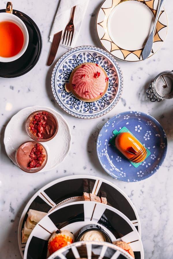 Vue supérieure de service à thé anglais d'après-midi comprenant le thé, la pâtisserie, les scones, la mousse et les couverts chau photos libres de droits