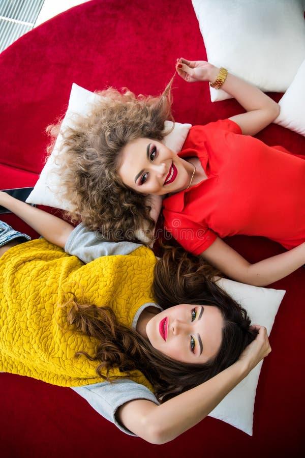 Vue supérieure de sofa menteur de l'OM de deux de sourire femmes d'amis avec le sourire photos libres de droits
