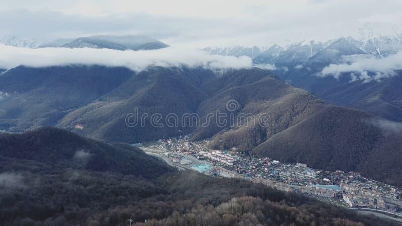 Vue supérieure de station de vacances près des montagnes avec les crêtes neigeuses Petite station de sports d'hiver au bas de la  photo libre de droits
