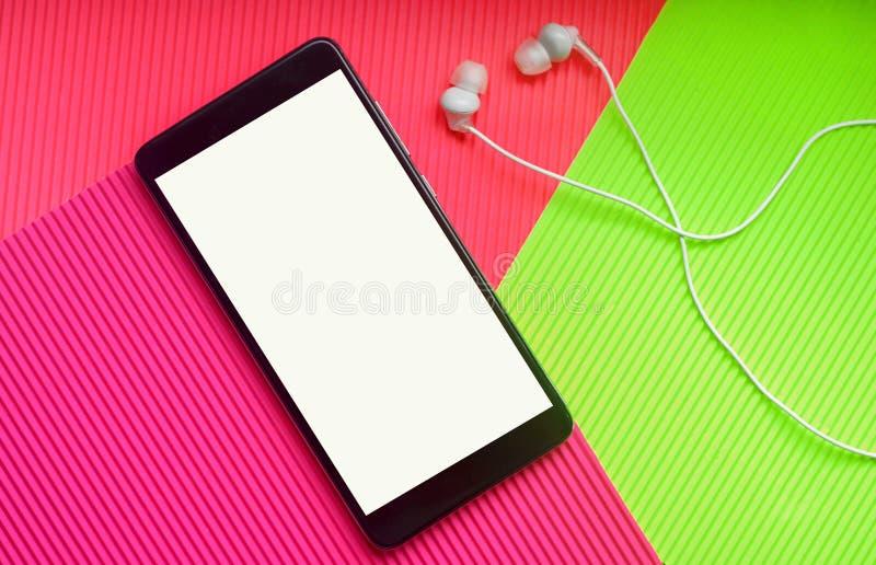 Vue supérieure de téléphone portable avec des écouteurs sur le fond vibrant multicolore à la mode image stock