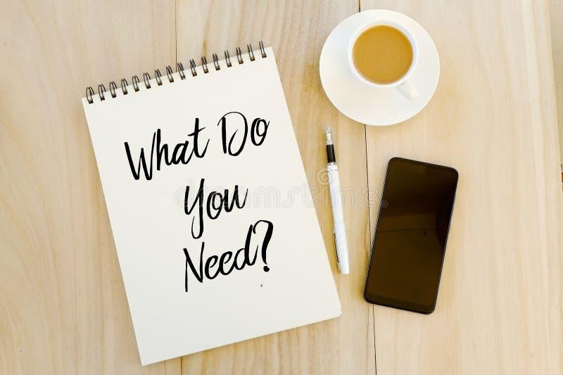 Vue supérieure de téléphone portable, de stylo, d'une tasse de café, et du carnet écrit avec la question ce qui vous ont besoin ? photographie stock libre de droits