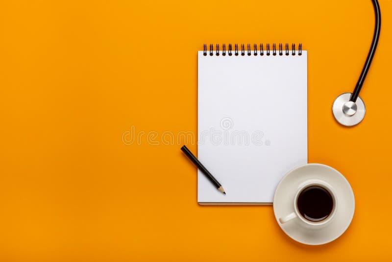 Vue supérieure de table de bureau de docteur avec le stéthoscope, le café et le papier blanc sur le presse-papiers avec le stylo images stock