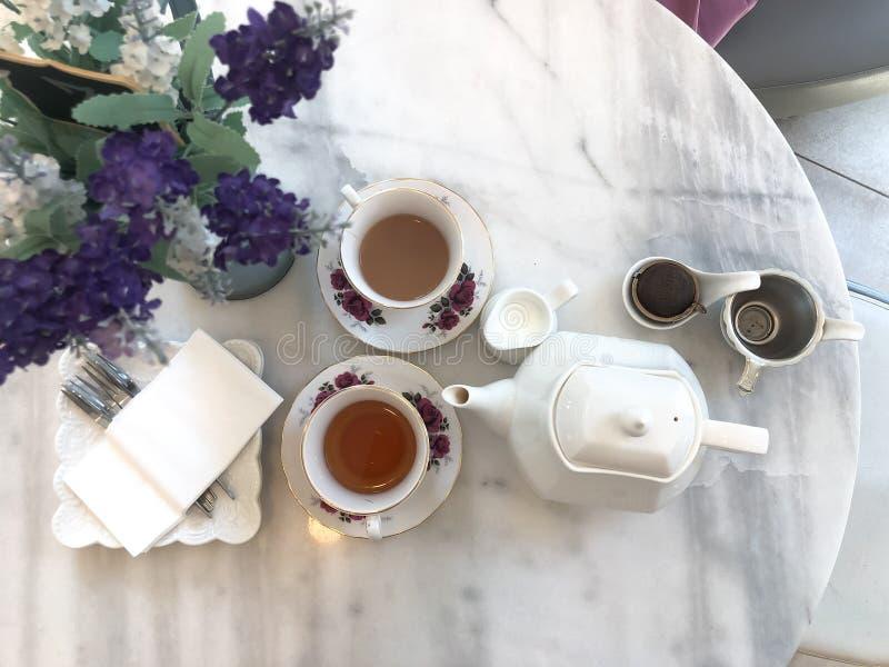 Vue supérieure de thé au lait chaud et le pot, temps de pause café sur la table de marbre photos stock