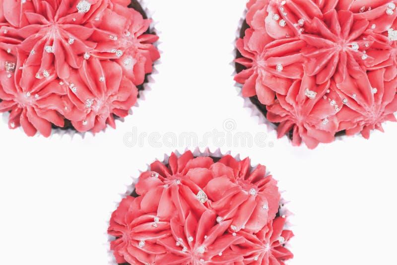 Vue supérieure de trois petits gâteaux avec le glaçage rose sur le fond blanc d'isolement photos libres de droits