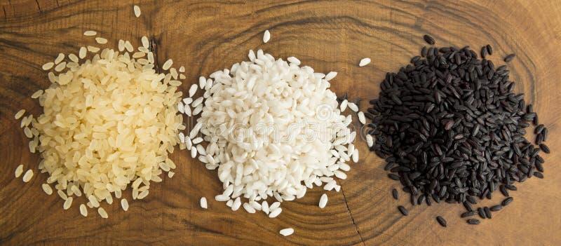 Vue supérieure de trois variétés de riz sur le fond en bois photos libres de droits