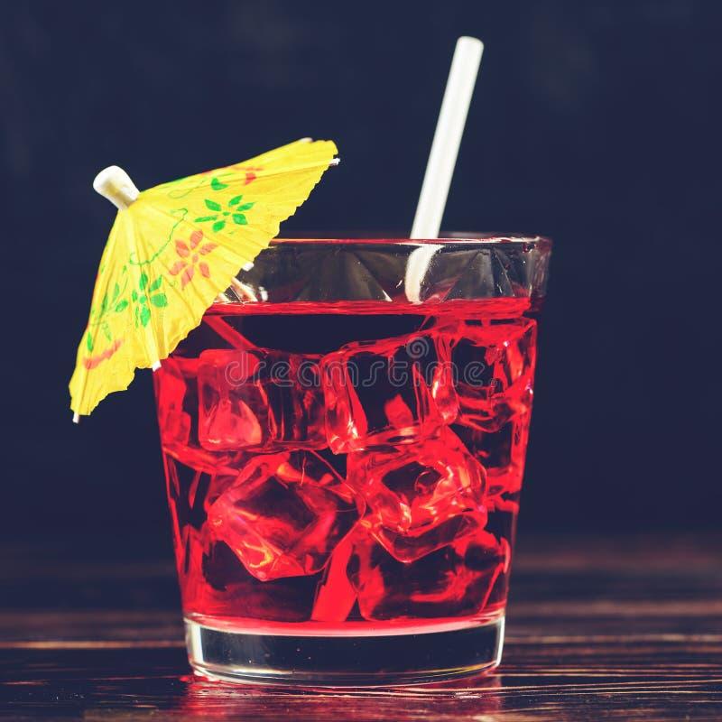 Vue supérieure de verre de cocktail rouge avec les glaçons et l'umbre de paille photo stock