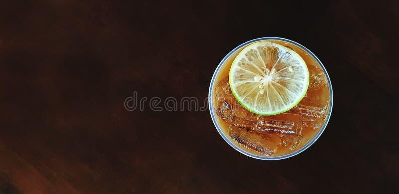 Vue supérieure de verre en plastique de thé glacé de citron avec la chaux ou le citron découpée en tranches photos libres de droits