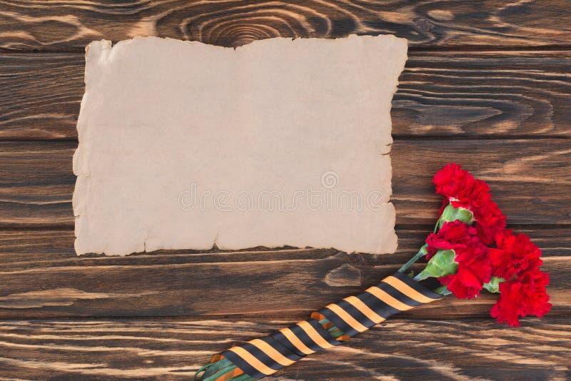 vue supérieure de vieux papier vide et d'oeillets enveloppés par le ruban de St George photos stock