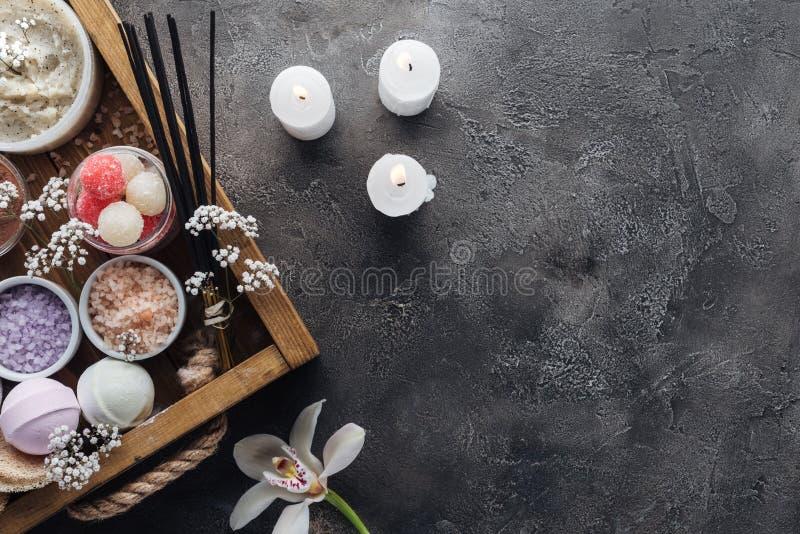 vue supérieure des accessoires de station thermale et de bain dans la boîte en bois et bougies brûlantes sur le gris image stock