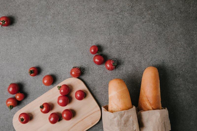 vue supérieure des baguettes dans des sacs en papier, des tomates fraîches et le conseil en bois sur le gris image libre de droits
