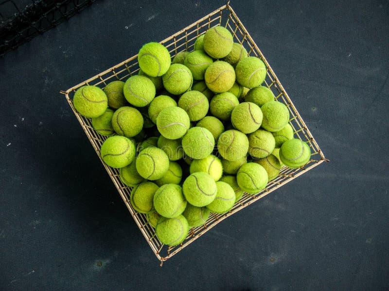 Vue supérieure des balles de tennis vertes dans un panier sur le terrain de jeu photos libres de droits