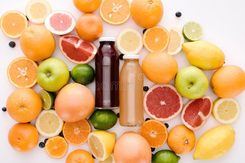 vue supérieure des bouteilles de jus frais avec les tranches mûres d'agrumes photographie stock