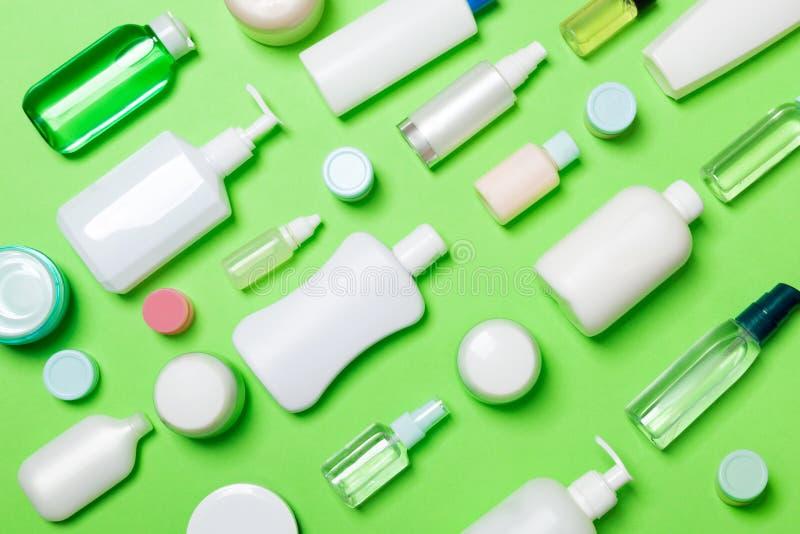 Vue supérieure des bouteilles et du conteneur cosmétiques différents pour des cosmétiques sur le fond vert Composition plate en c photo libre de droits