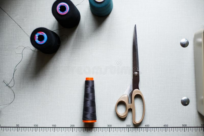 Vue supérieure des ciseaux et des écheveaux du fil sur une table blanche avec des inscriptions Industrie de couture Fabrication d photographie stock