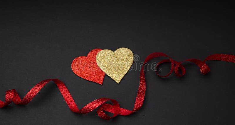 Vue supérieure des coeurs rouges et d'or avec le ruban, fond noir, d'isolement photos libres de droits