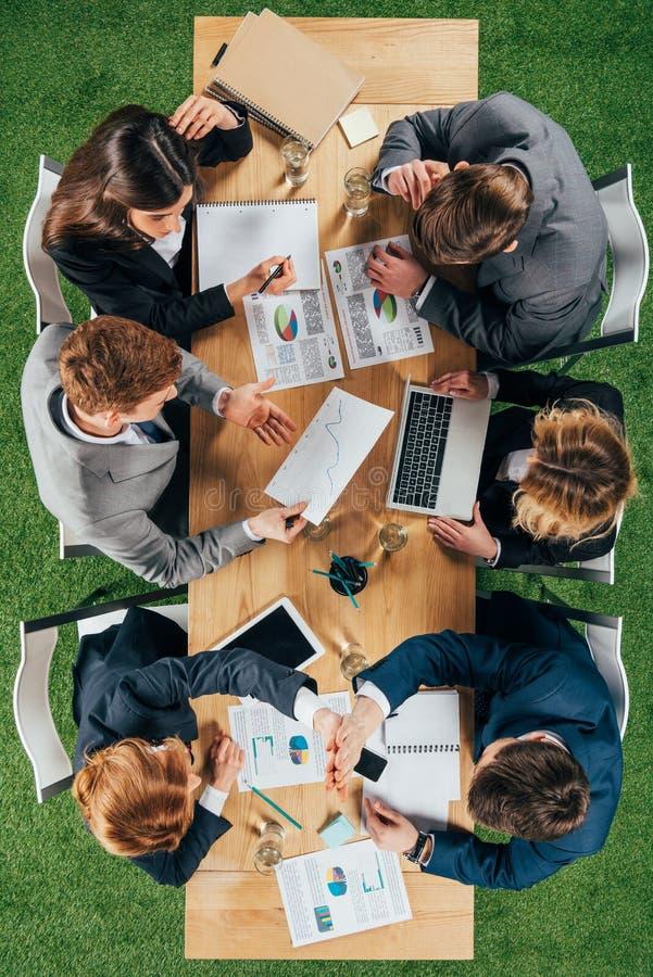 Vue supérieure des collègues d'affaires ayant la réunion à la table avec des documents et des dispositifs photos libres de droits