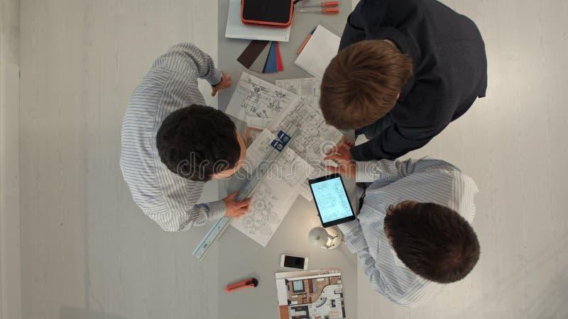 Vue supérieure des constructeurs discutant le modèle à l'intérieur Concept de bâtiment, de rénovation, de réparation, de travail  images stock