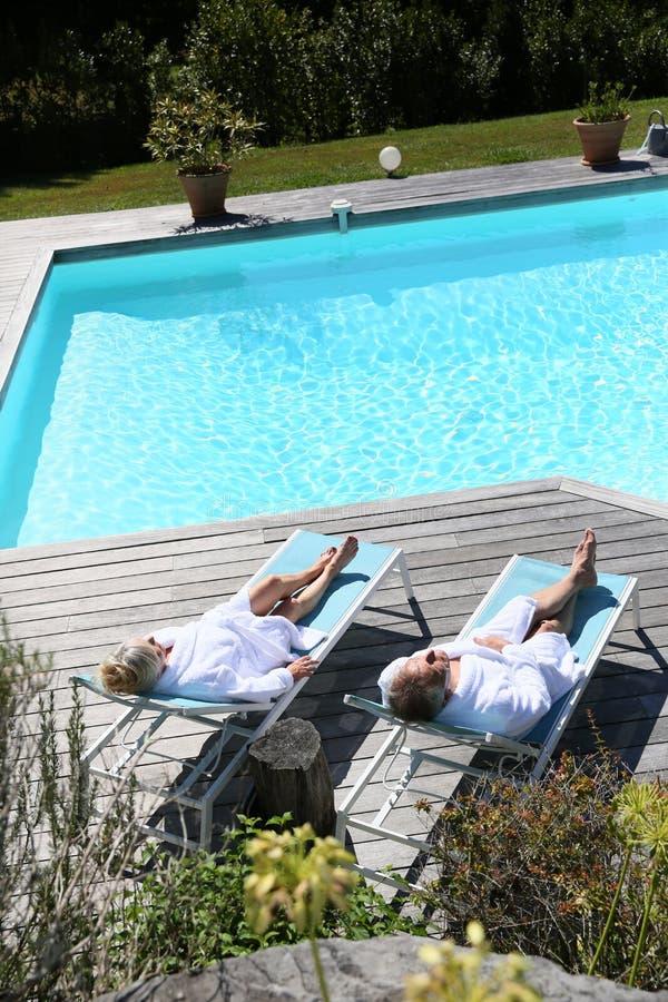 Vue supérieure des couples supérieurs détendant par la piscine photos stock