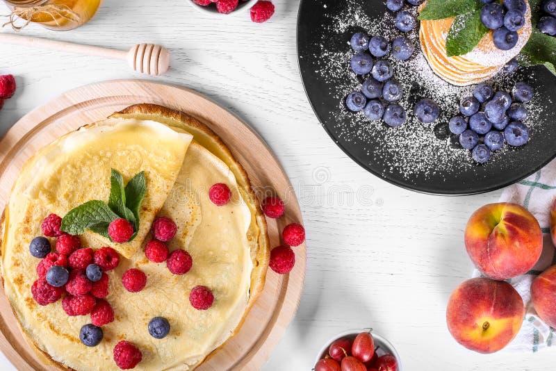 Vue supérieure des crêpes avec des framboises et des myrtilles Petit déjeuner sain d'été, crêpes russes classiques faites maison, images libres de droits