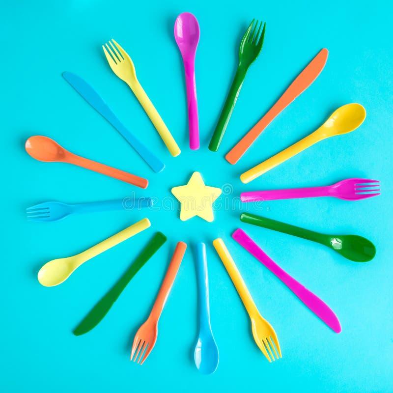 Vue supérieure des cuillères, des fourchettes et des couteaux en plastique multicolores avec l'étoile jaune d'isolement sur le bl photo libre de droits