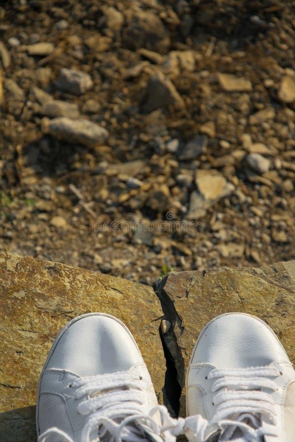 Vue supérieure des espadrilles blanches sur une roche de montagne photographie stock