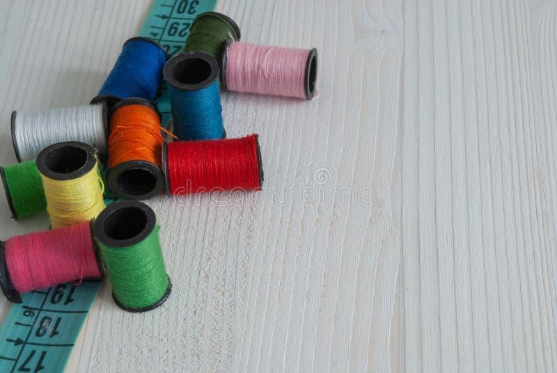 Vue supérieure des fils colorés et du ruban métrique photos stock