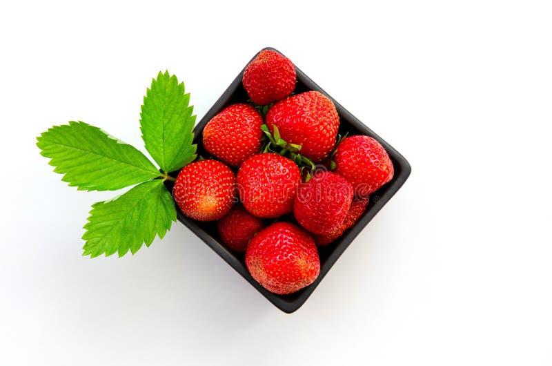 Vue supérieure des fraises espagnoles savoureuses fraîchement rassemblées sur une boîte d'isolement sur le fond blanc image libre de droits