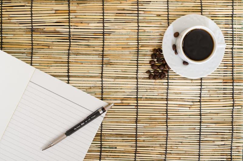 Vue supérieure des grains de café avec la tasse blanche, le carnet vide et le stylo sur le tapis images libres de droits