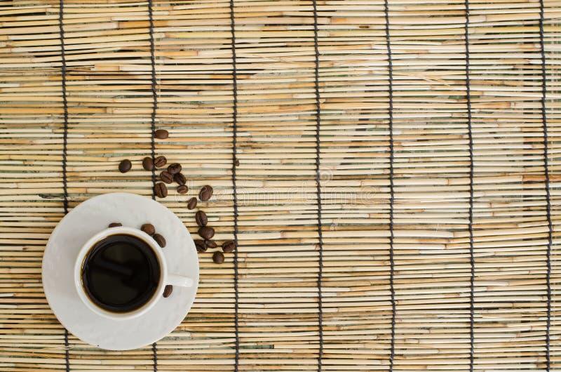 Vue supérieure des grains de café avec la tasse blanche sur le tapis du Japon photographie stock