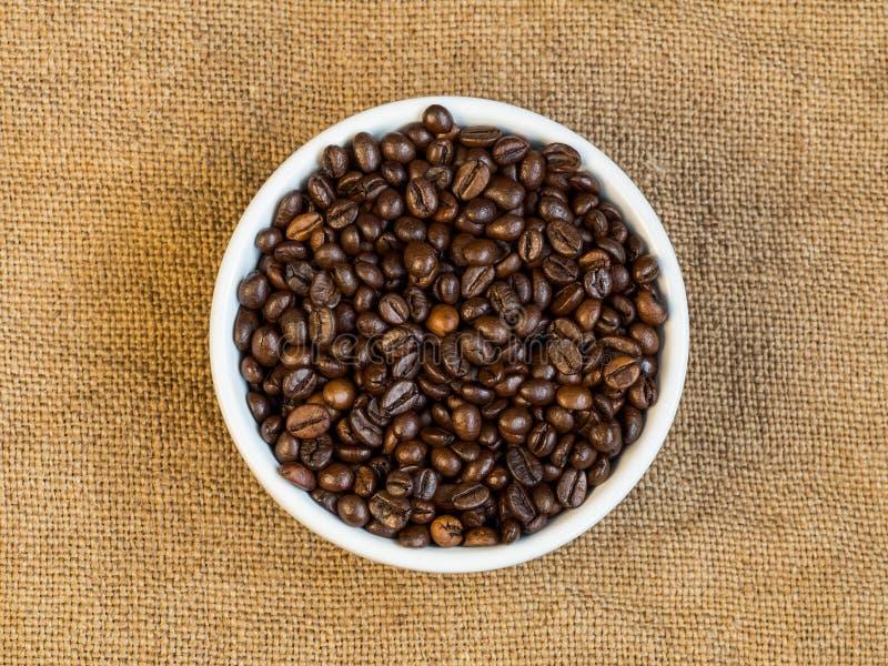 Vue supérieure des grains de café d'arabica dans la cuvette en céramique sur le Ba de toile à sac images libres de droits