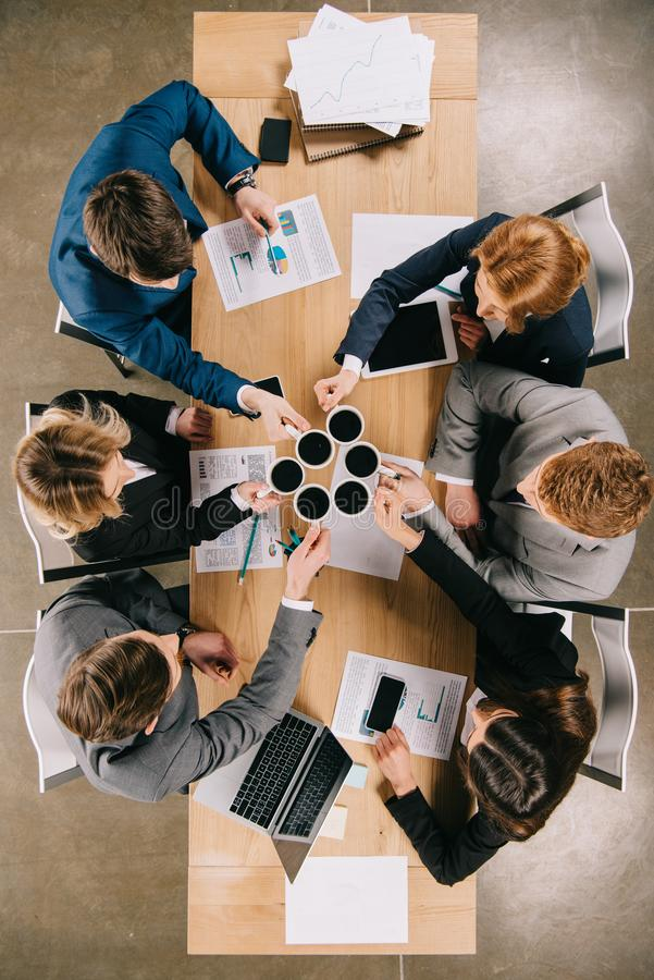 Vue supérieure des hommes d'affaires avec des tasses de café dans des mains se reposant à la table avec les dispositifs numérique photos libres de droits