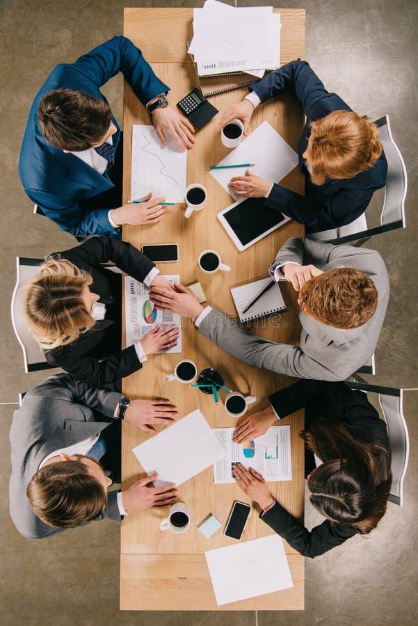 Vue supérieure des hommes d'affaires discutant à la table avec les tasses de café numériques de dispositifs photos stock