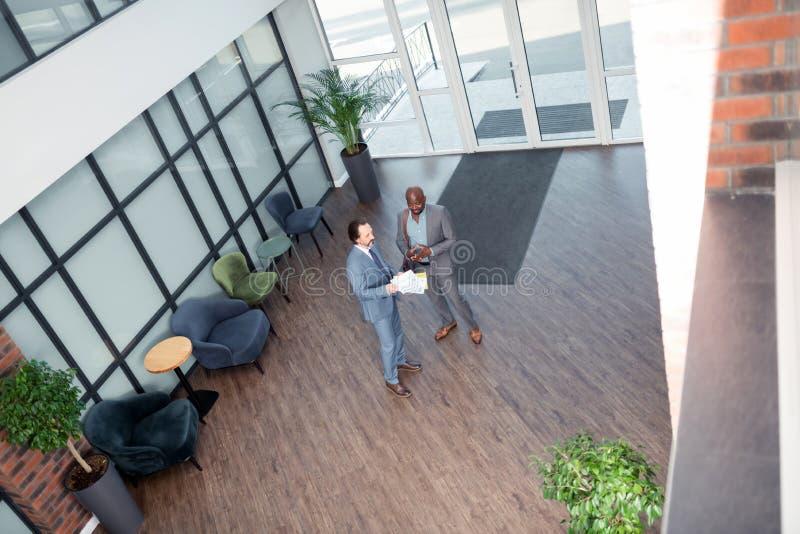 Vue supérieure des hommes d'affaires lisant l'accord après la réunion photos libres de droits