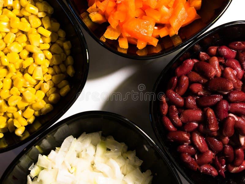 Vue supérieure des ingrédients de nourriture dans des cuvettes noires : oignon doux coupé, poivron rouge doux coupé, maïs en boît photo libre de droits