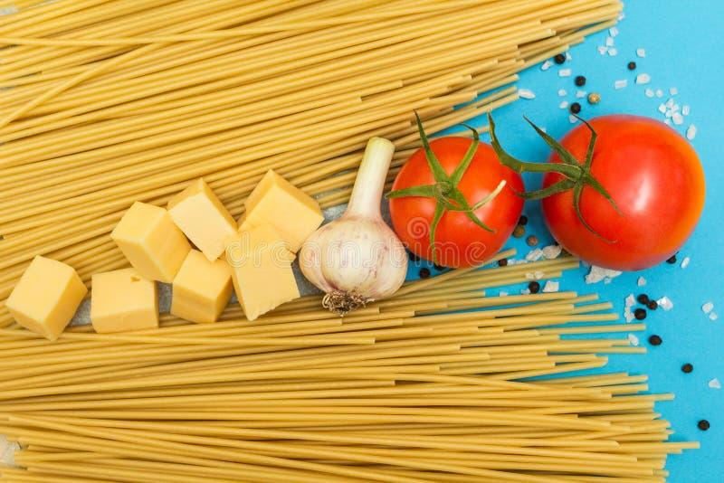 Vue supérieure des ingrédients italiens des tomates de pâtes et de légumes, pâtes, ail, poivre, fromage, épices sur un fond bleu photos libres de droits