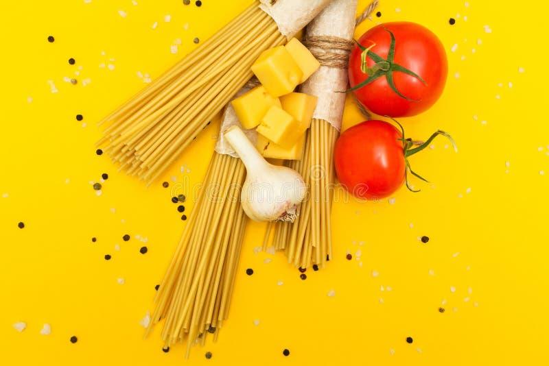 Vue supérieure des ingrédients italiens des tomates de pâtes et de légumes, pâtes, ail, poivre, fromage, épices sur un fond jaune photo libre de droits