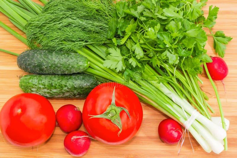 Vue supérieure des légumes et des verts sur la planche à découper en bambou image libre de droits