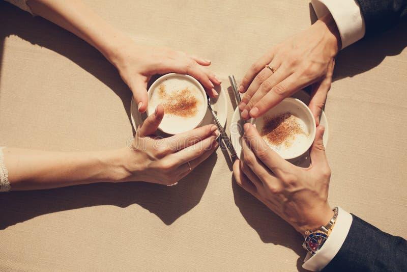 Vue supérieure des mains d'un homme et d'une femme tenant une tasse de café sur une table, un jour ensoleillé extérieur photos stock