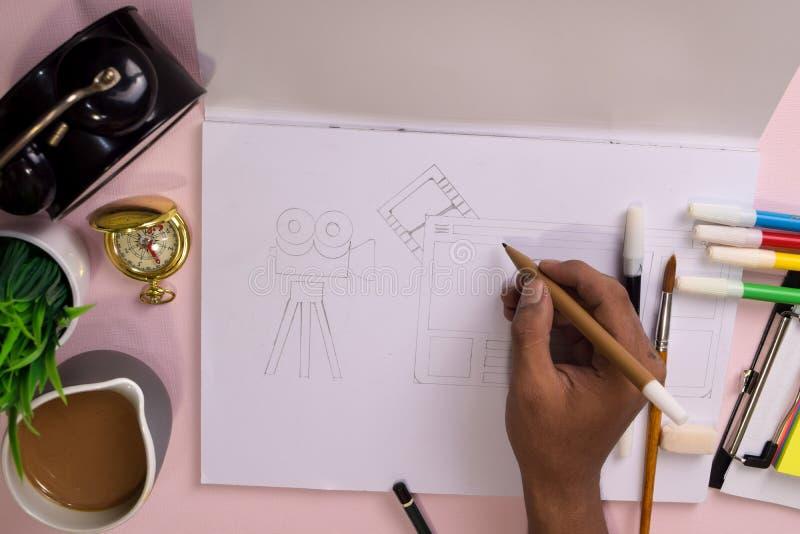 Vue supérieure des mains de l'homme dessinant sur une table rose, préparant pour faire le travail dans un carnet ouvert photo stock