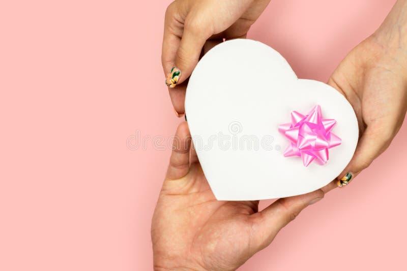 Vue supérieure des mains masculines et femelles tenant le boîte-cadeau de coeur de forme avec l'arc rose sur le jaune Présent pou photographie stock